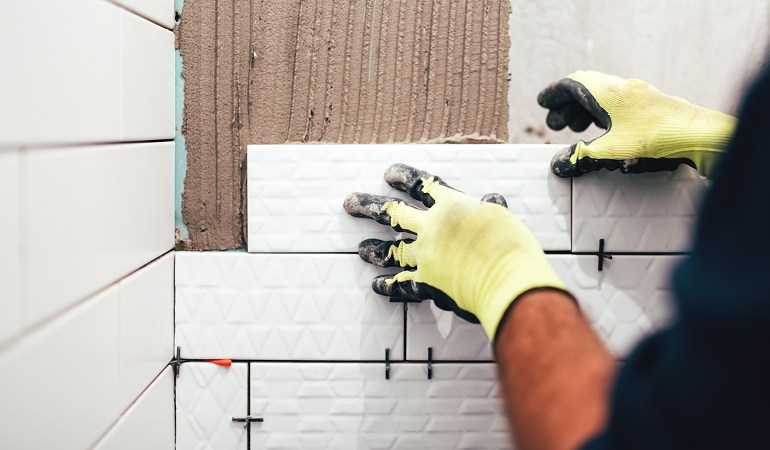 construction worker installing small ceramic tiles on bathroom walls and applying mortar with trowel