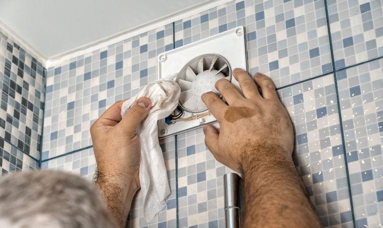 wiping away dirt bathroom extractor fan blades